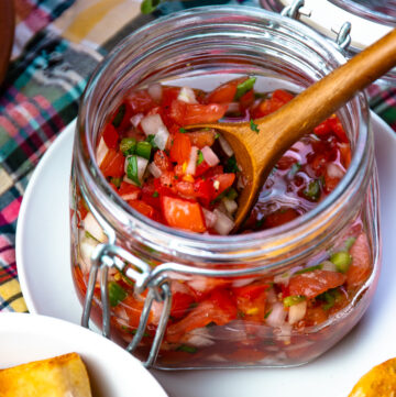 Tomato Relish in a jar with a wooden spoon for serving.