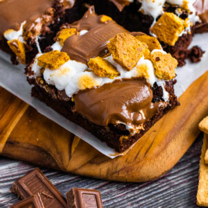 Smores Brownies on a cutting board with parchment paper for serving.