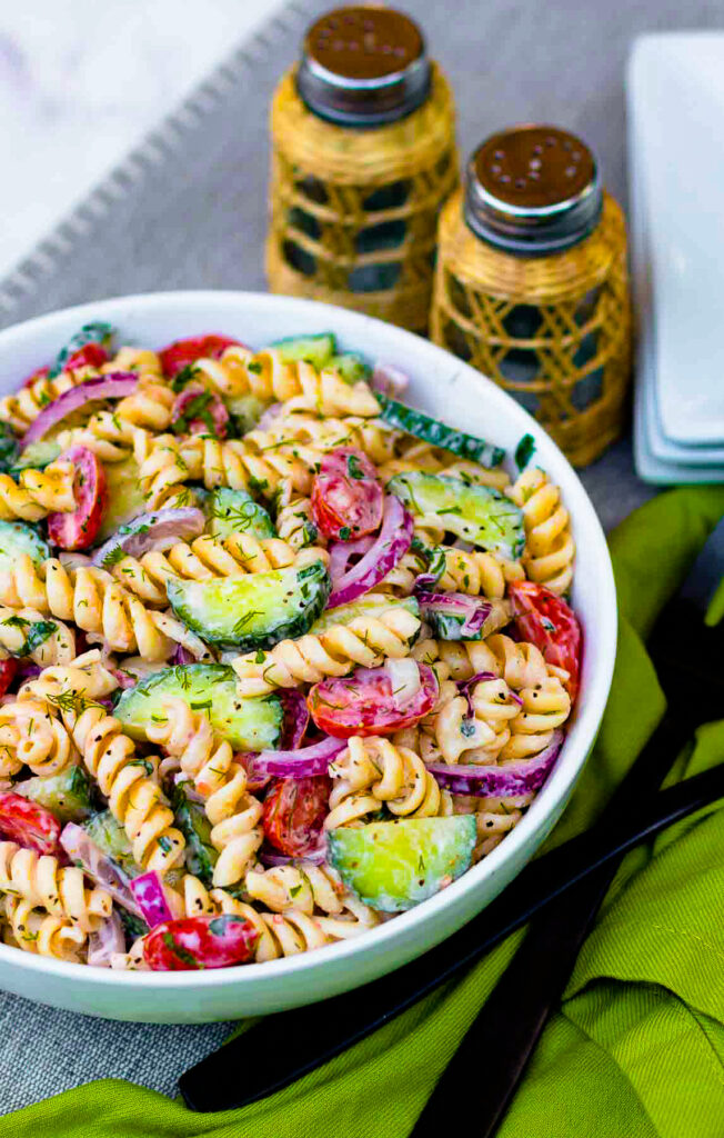Creamy Tomato Cucumber Pasta Salad made with a simple dressing with fresh herbs and red onions.