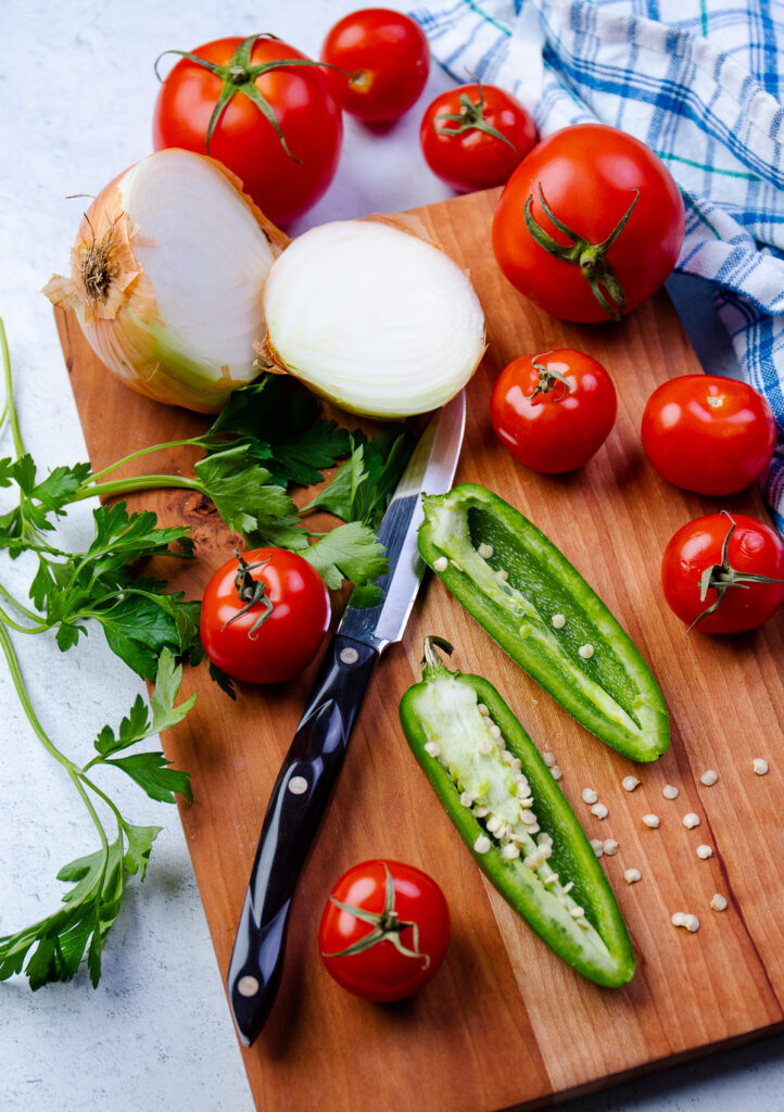 Tomatos, onion, jalapeno and parsley on a cutting board with a knife.