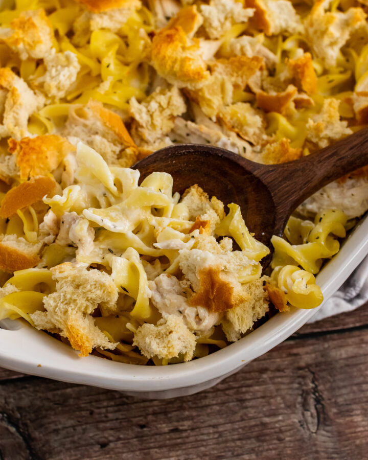 Creamy Chicken Casserole in a white casserole dish with a wooden spoon for serving.