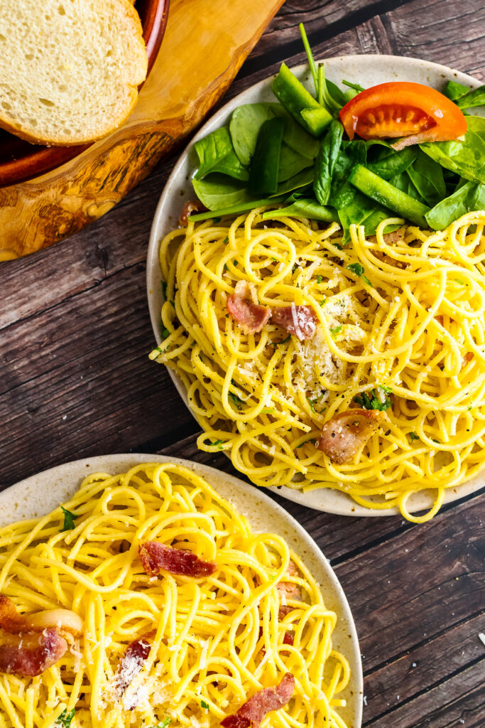 Two plates of Pasta Carbonara served with spinach and tomatoes.