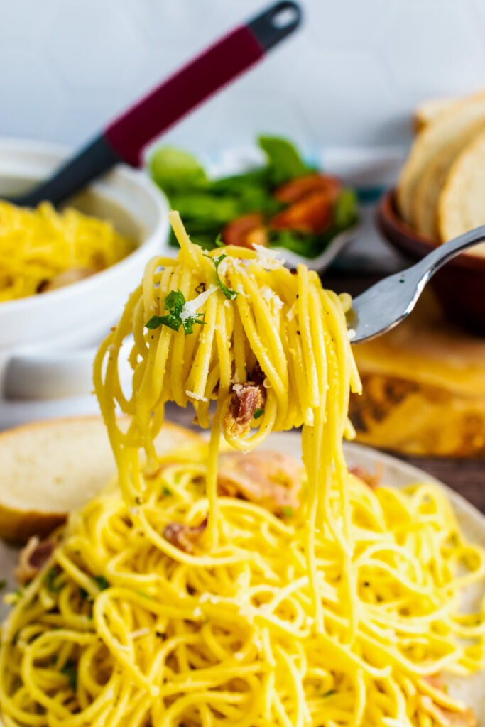 Pasta Carbonara on a fork with bacon and parsley garnigh