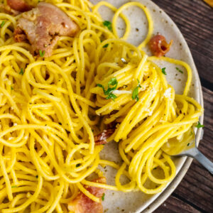 Pasta Carbonara on a plate twirled with a fork served with bread.