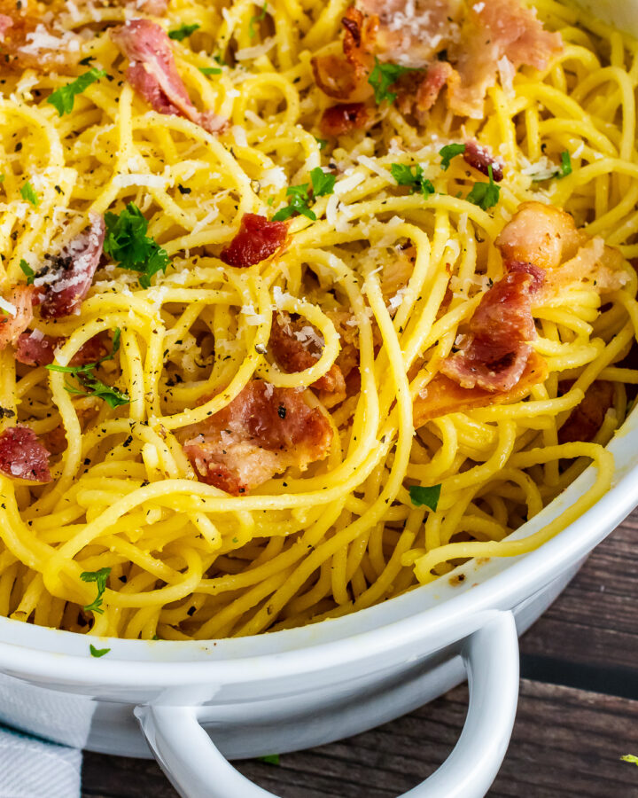 Pasta Carbonara in a white pot with bacon and cheese.