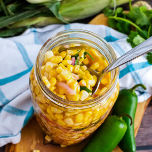 Pickled Corn with red onions and jalapenos in a jar served with a spoon.