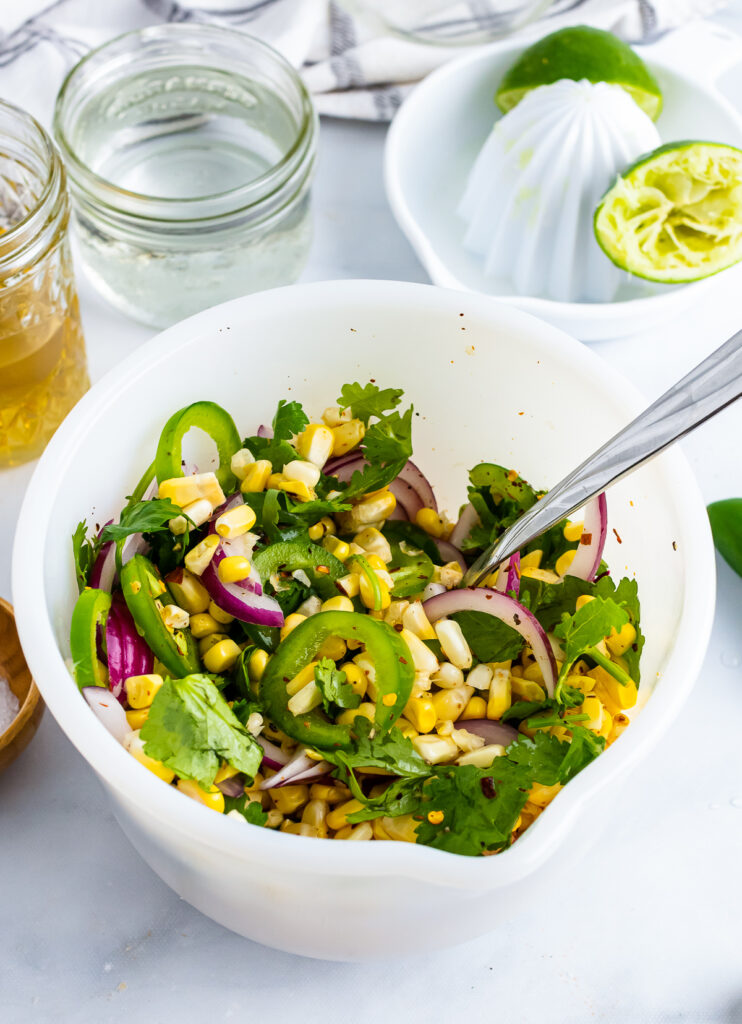 Corn, jalapenose, cilantro, jalapens mixed together in a whitle bowl for Pickled Corn.