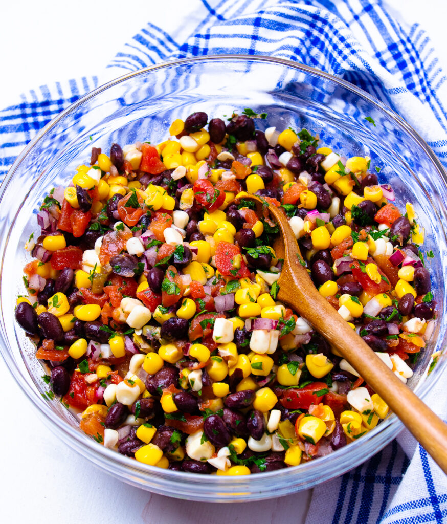 Glass bowl with woodend spoon in black bean and corn salsa.