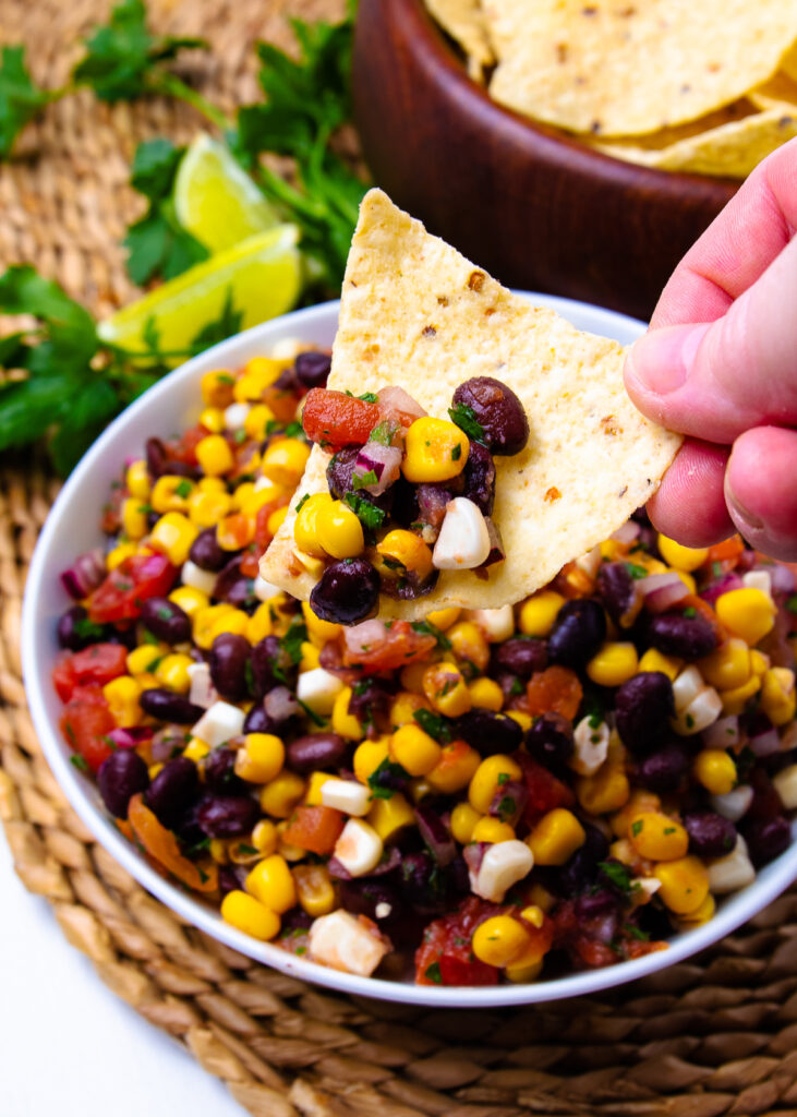 Tortill chip held with hand and black bean and corn salsa