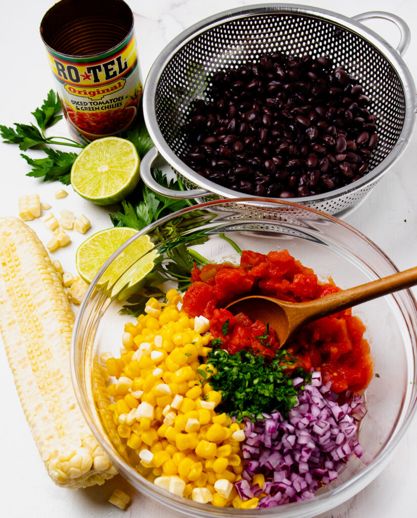 Corn, black beans, parsley, red onion and tomatoes for salsa recipe.