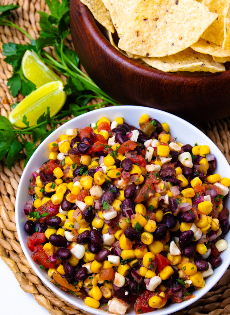 White bowl with black beans and corn salsa and brown bowl with tortilla chips.