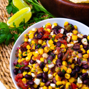 Balck Bean and Corn Salsa in a white bowl with limes for garnish.