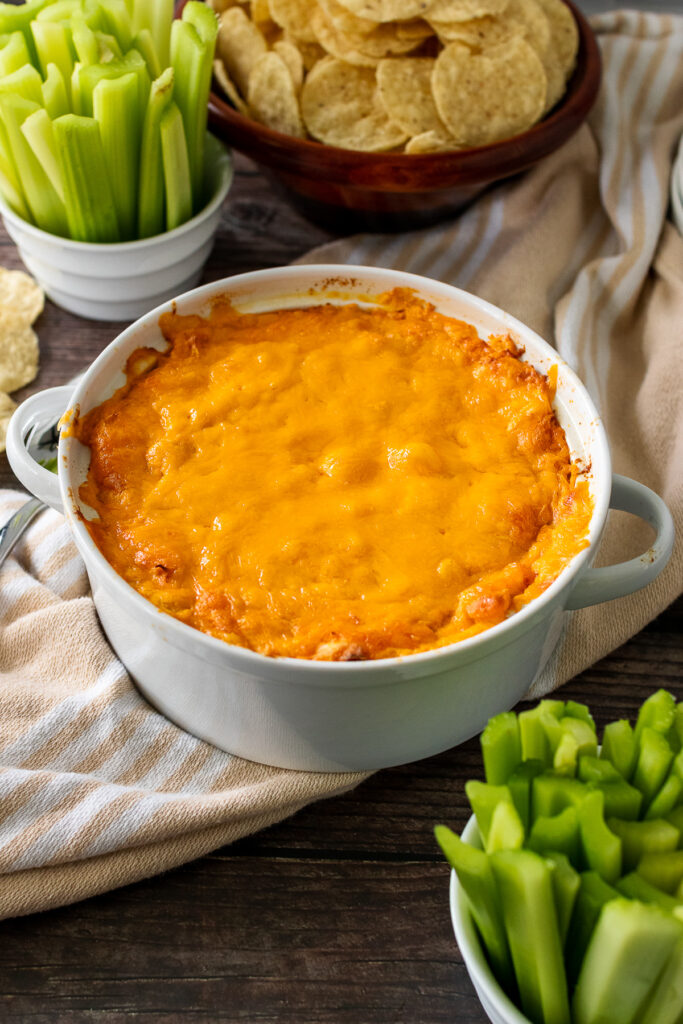 White bowl with baked Buffalo Chicken Dip served with celery sticks and chips.