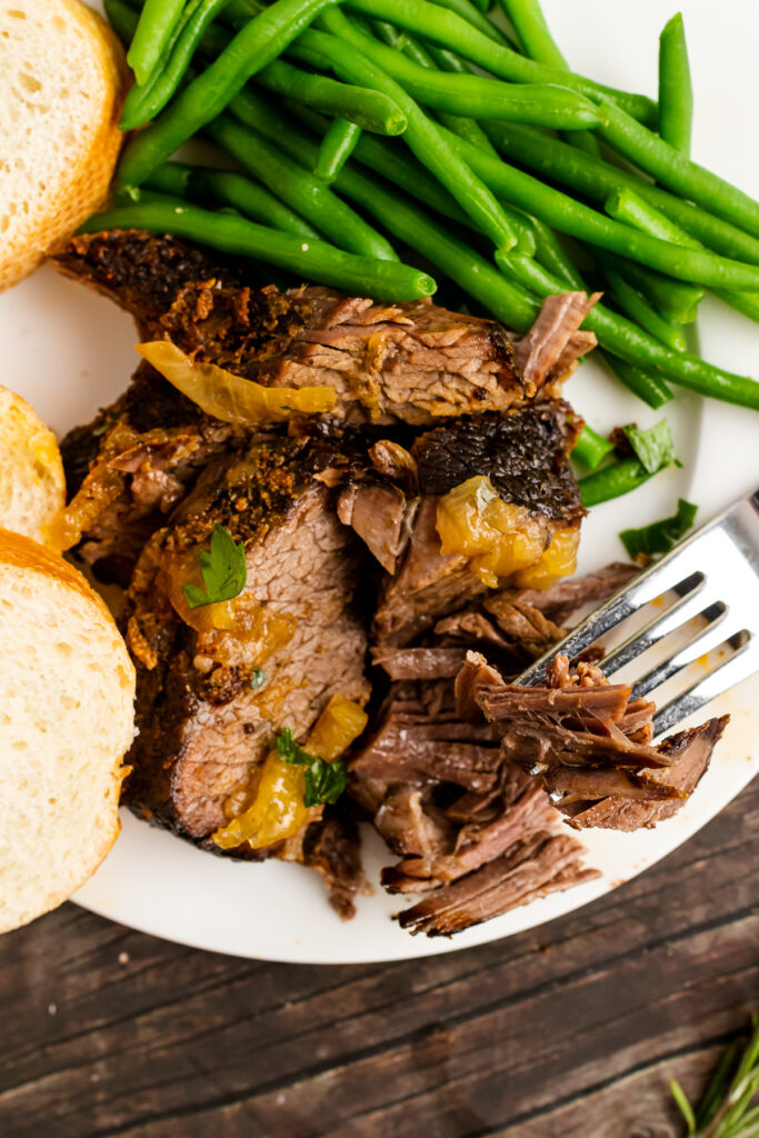 Busy Day Pot Roast on a white plate with a fork and green beans