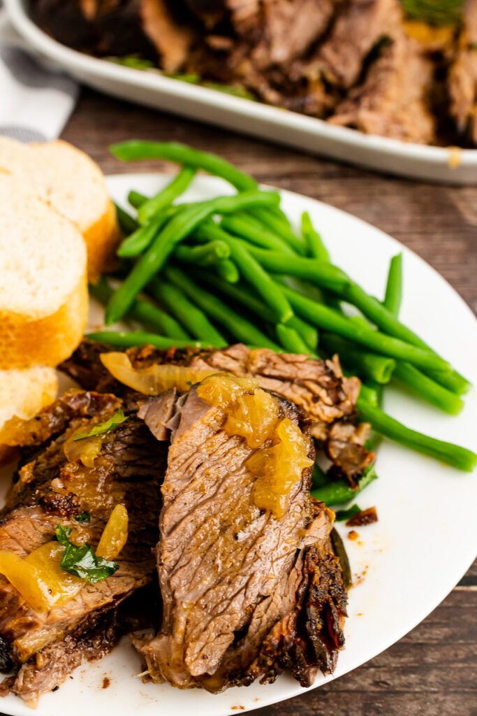Sliced Pot Roast with onion, green bean and bread on a white plate.