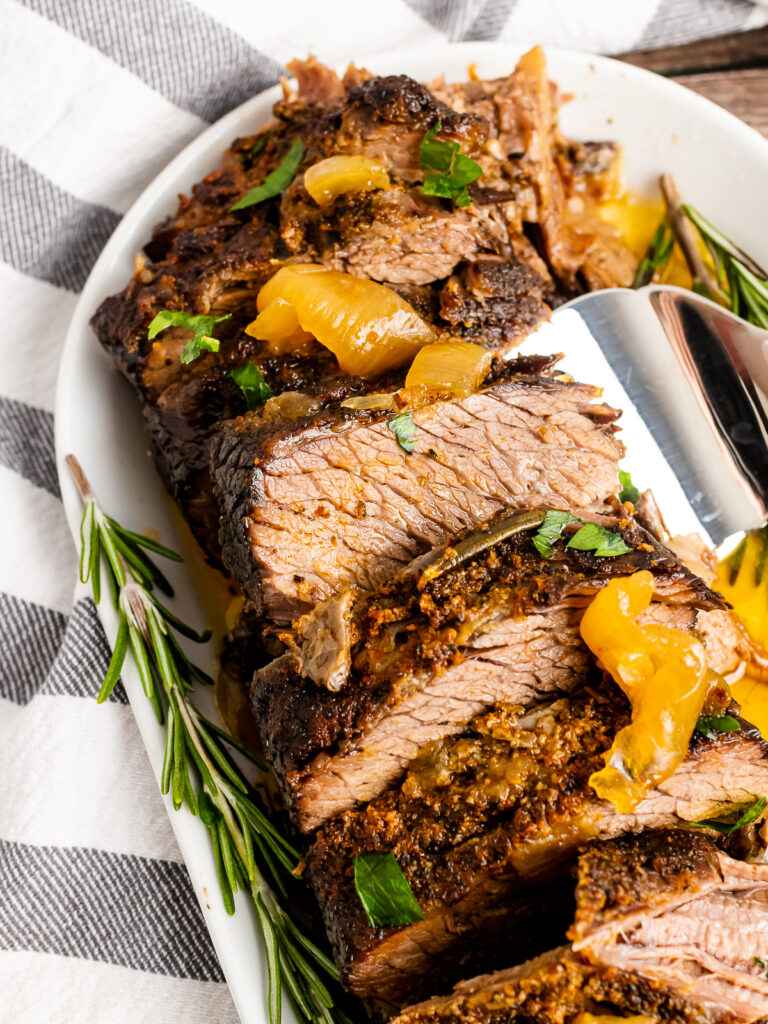 Sliced Slow Cooker Pot Roast with onions and fresh rosemary and a serving spoon.