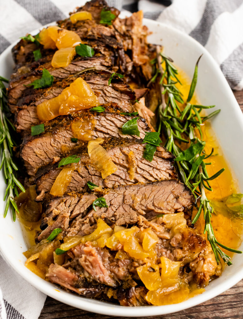 Slow Cooker Pot Roast on a white platter with fresh rosemary.