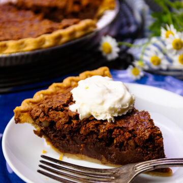 Slice of Chocolate Chess Pie with pecans on a white plate with a fork.
