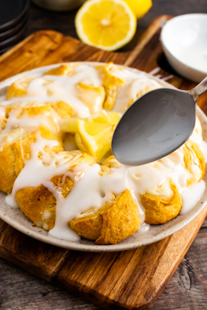 Baked cream cheese danish with lemon sugar icing drizzled with a spoon.