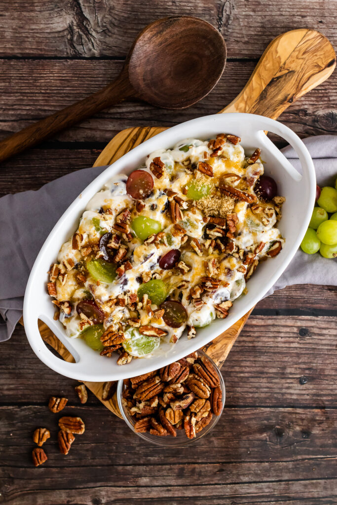 Grape Salad with chopped pecans on a wooden cutting board with a spoon.