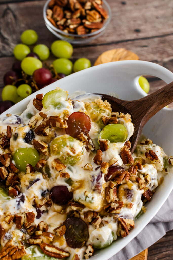 Grape Salad with chopped pecans in a white bowl with wooden spoon.
