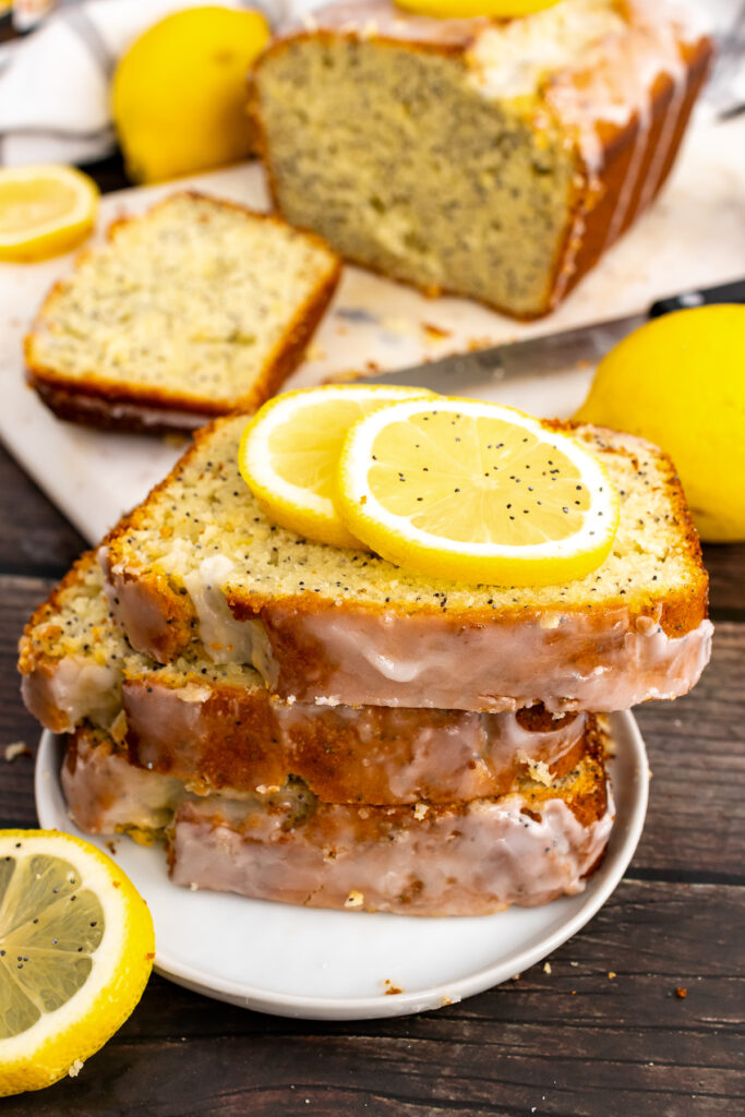 Slices of homemade Lemon Poppy Seed Cake on a small plate with lemon slices.