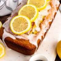 Lemon Poppy Seed Cake on a white board with lemon slices.