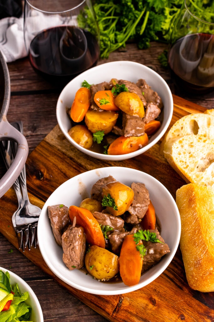 Two white bowls full of skillet beef stew served with bread and red wine.