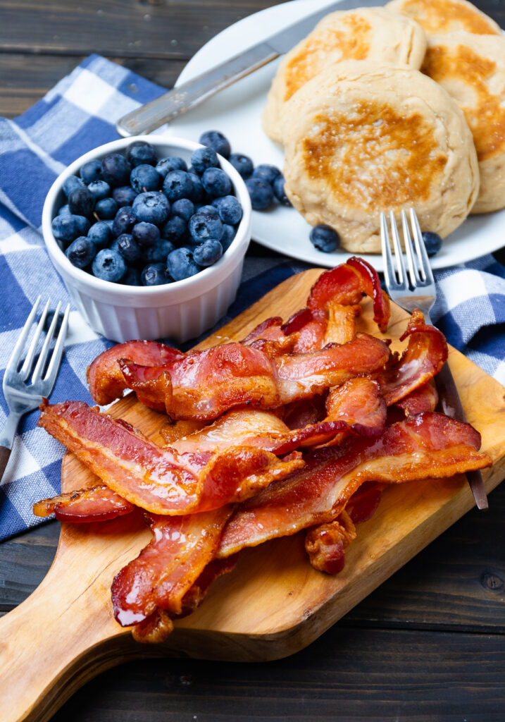 Pieces of cooked bacon with blueberries and english muffins for breakfast.