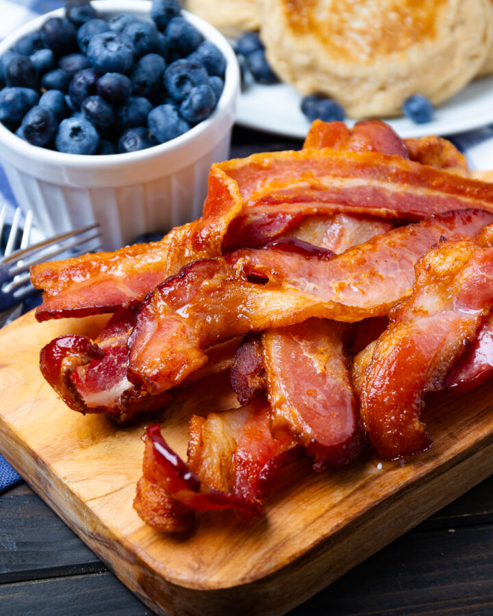 Air fried bacon on a wooden board.