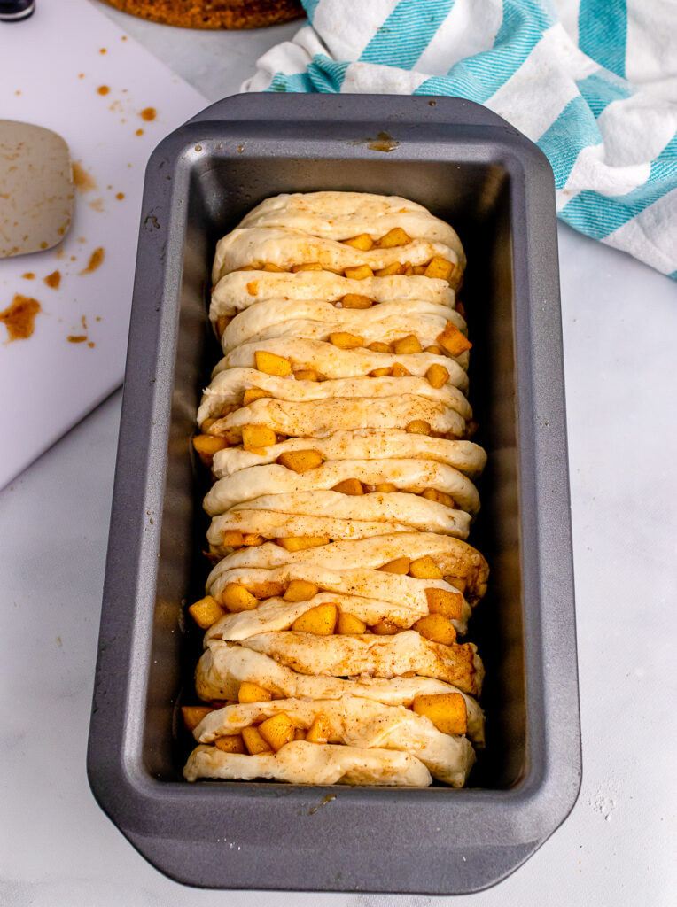 Unbaked apple cinnamon pull apart bread in a loaf pan.