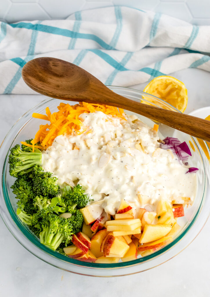 Broccoli Apple Salad ingredients in a bowl with salad dressing and a wooden spoon.
