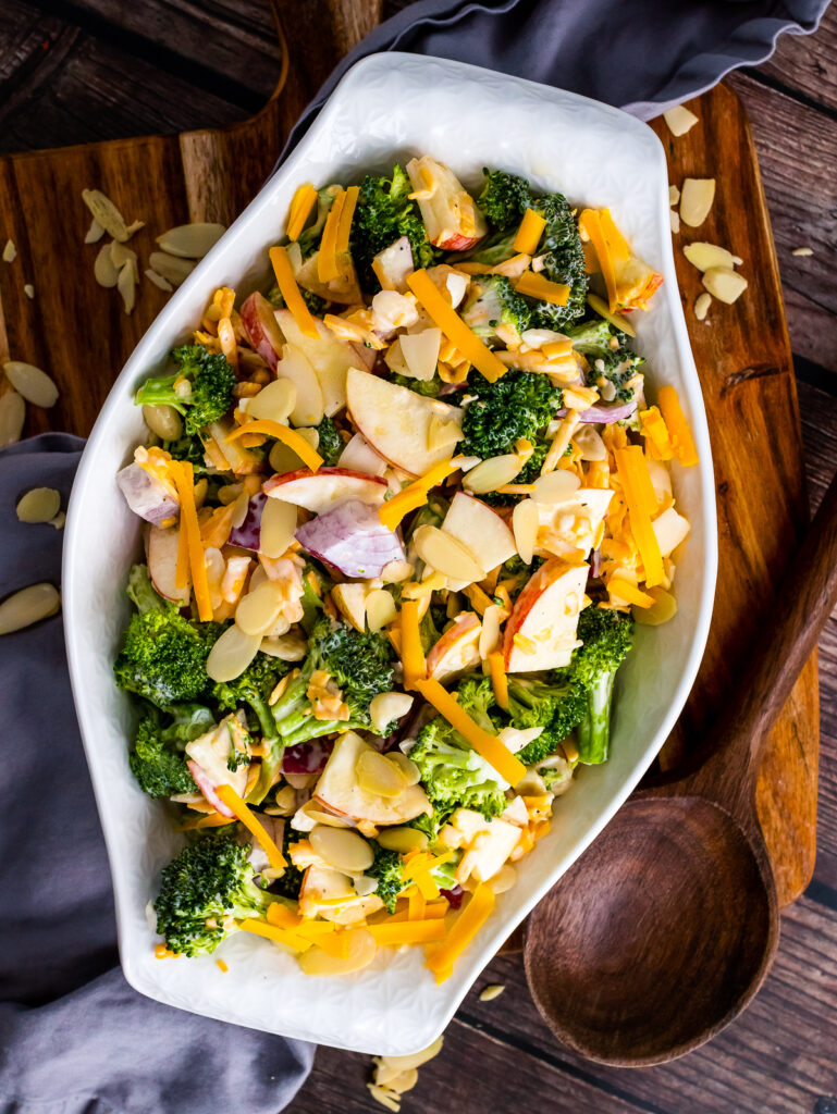 Overhead photo of Broccoli Apple Salad in a white serving bowl with a wooden spoon.