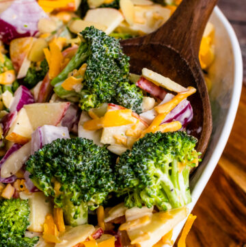 Broccoli Apple Salad with cheese and almonds on a wooden spoon.