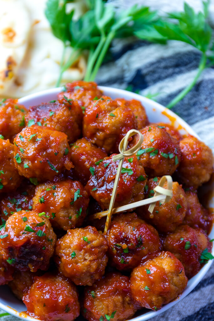 Bourbon Meatball in a white bowl with toothpicks for serving.