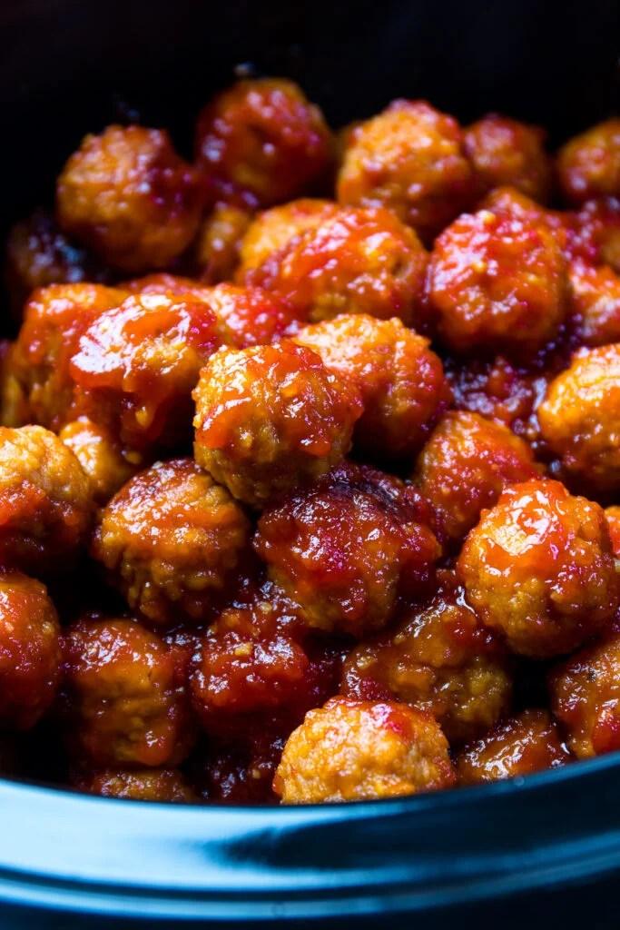 Bourbon Meatballs in a black crock pot with sauce.