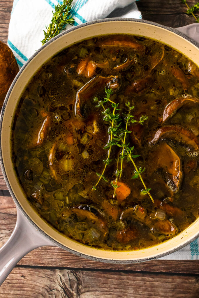 Gray stock pot with mushroom soup and fresh thyme.