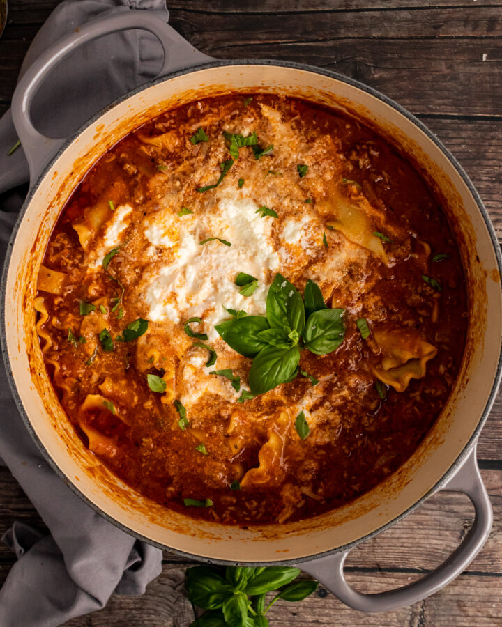 Gray stock pot with Lasagna Soup with ricotta cheese and fresh basil.