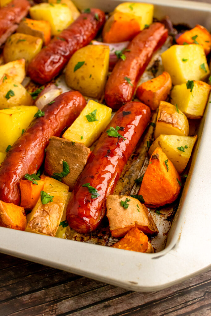 Cooked on a metal sheet pan are Brats with yellow and sweet potatoes.