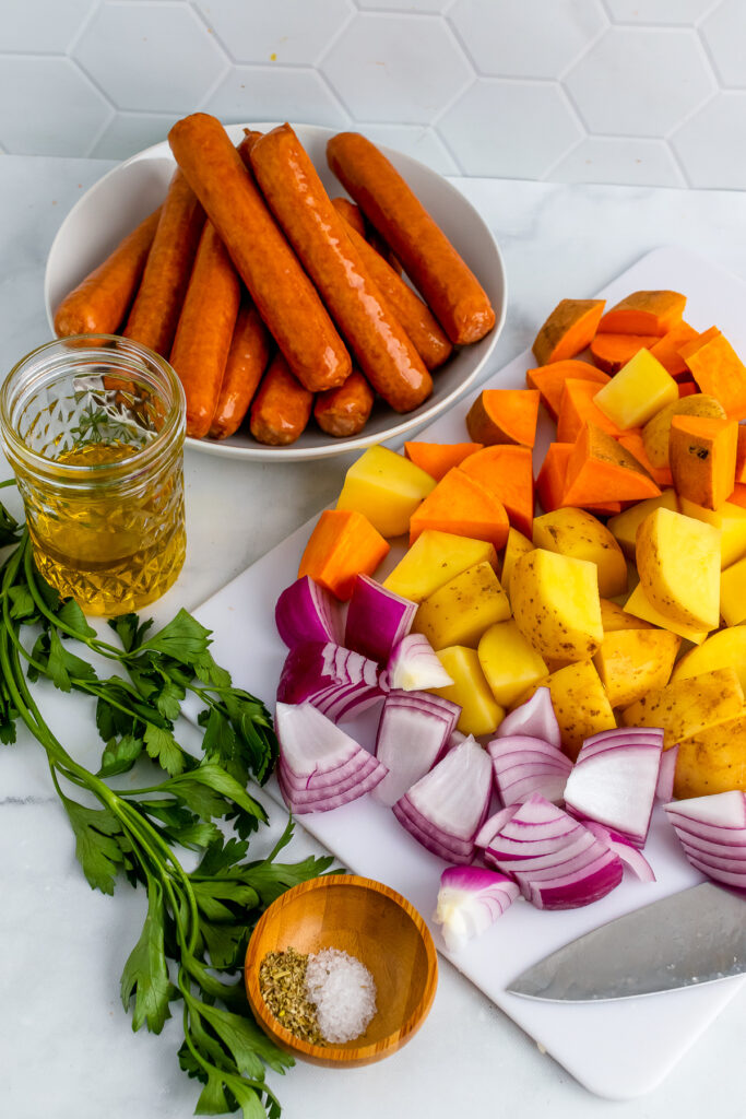 Beef brats, red onions, yellow and sweet potatoes with oil and seasoning.