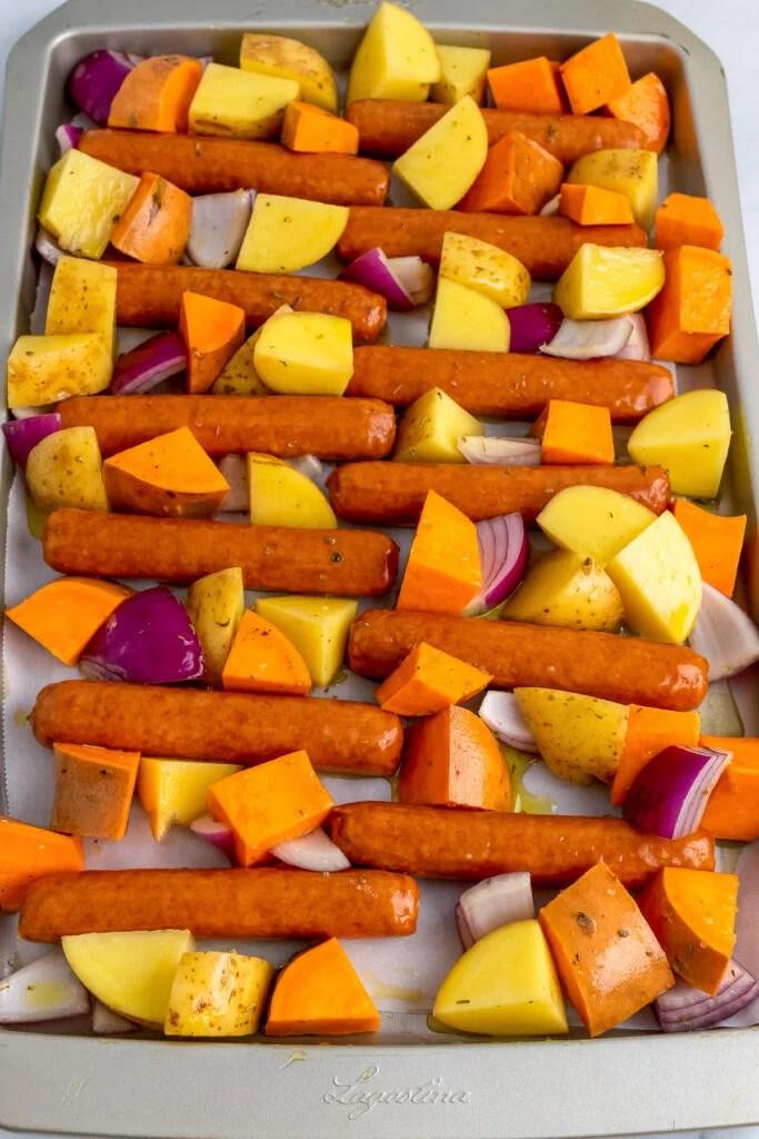 Brats, sweet potatoes, yellow potatoes and red onions on a sheet pan.