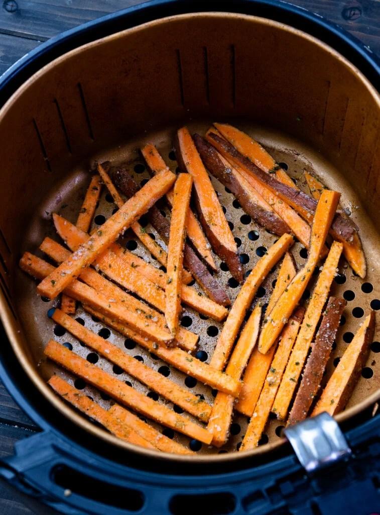 Basket of sweet potatoes in air fryer.