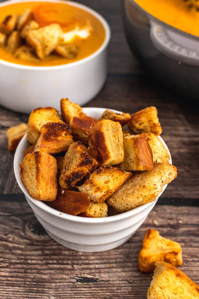 Homemade croutons in a white bowl.