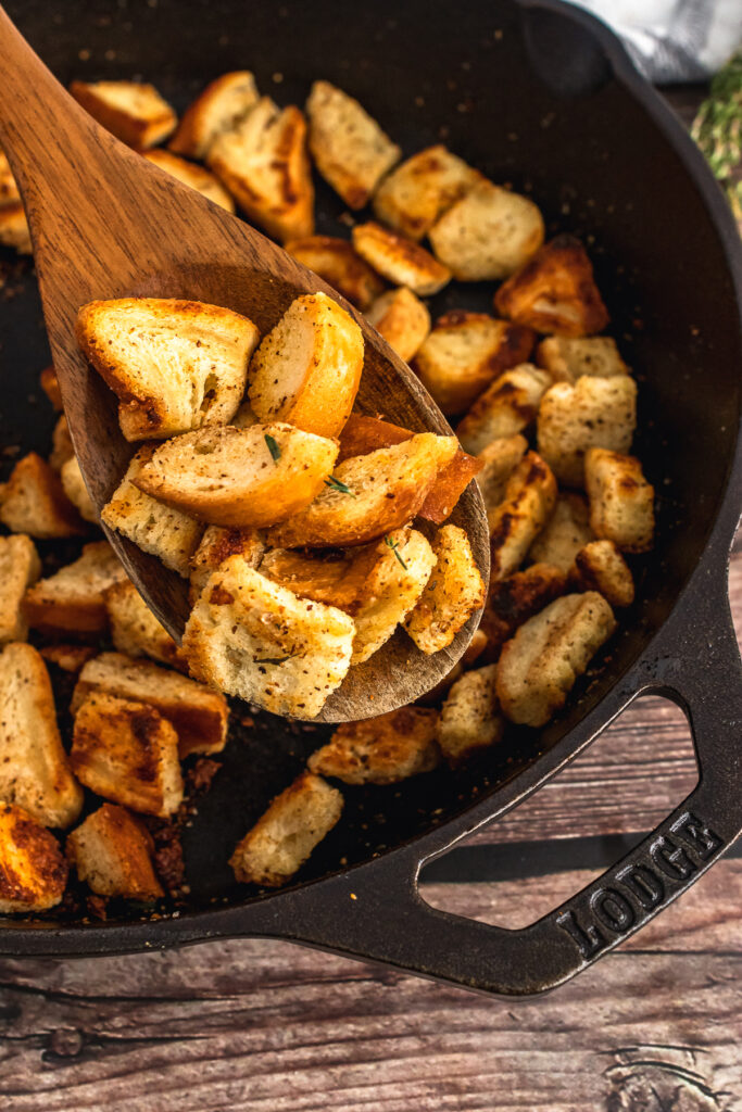 Homemade croutons served on a wooden spoon.