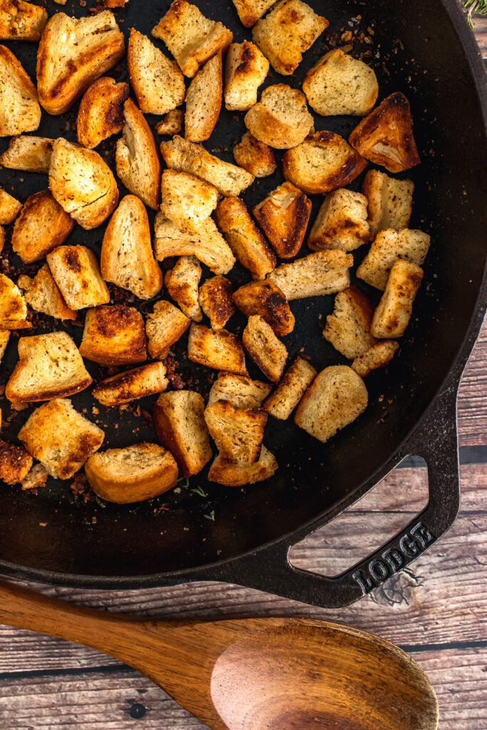 Homemade croutons in a cast iron skillet with a wooden spoon.