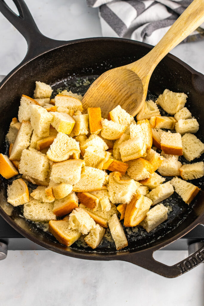 Bread cubes in butter sautéed in cast iron for croutons.