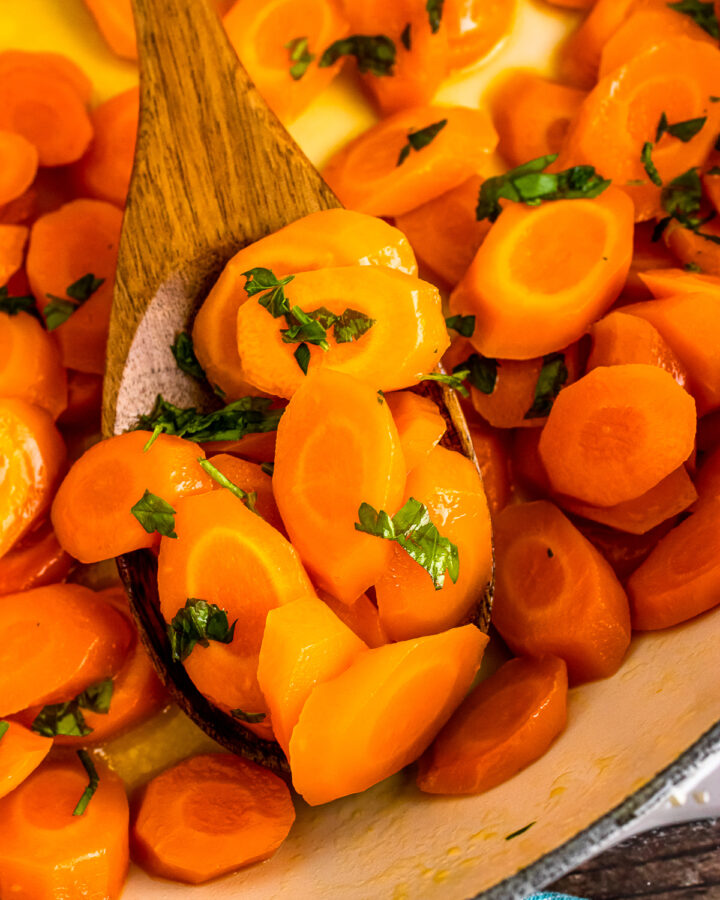 Easy to make glazed carrots served on a wooden spoon.