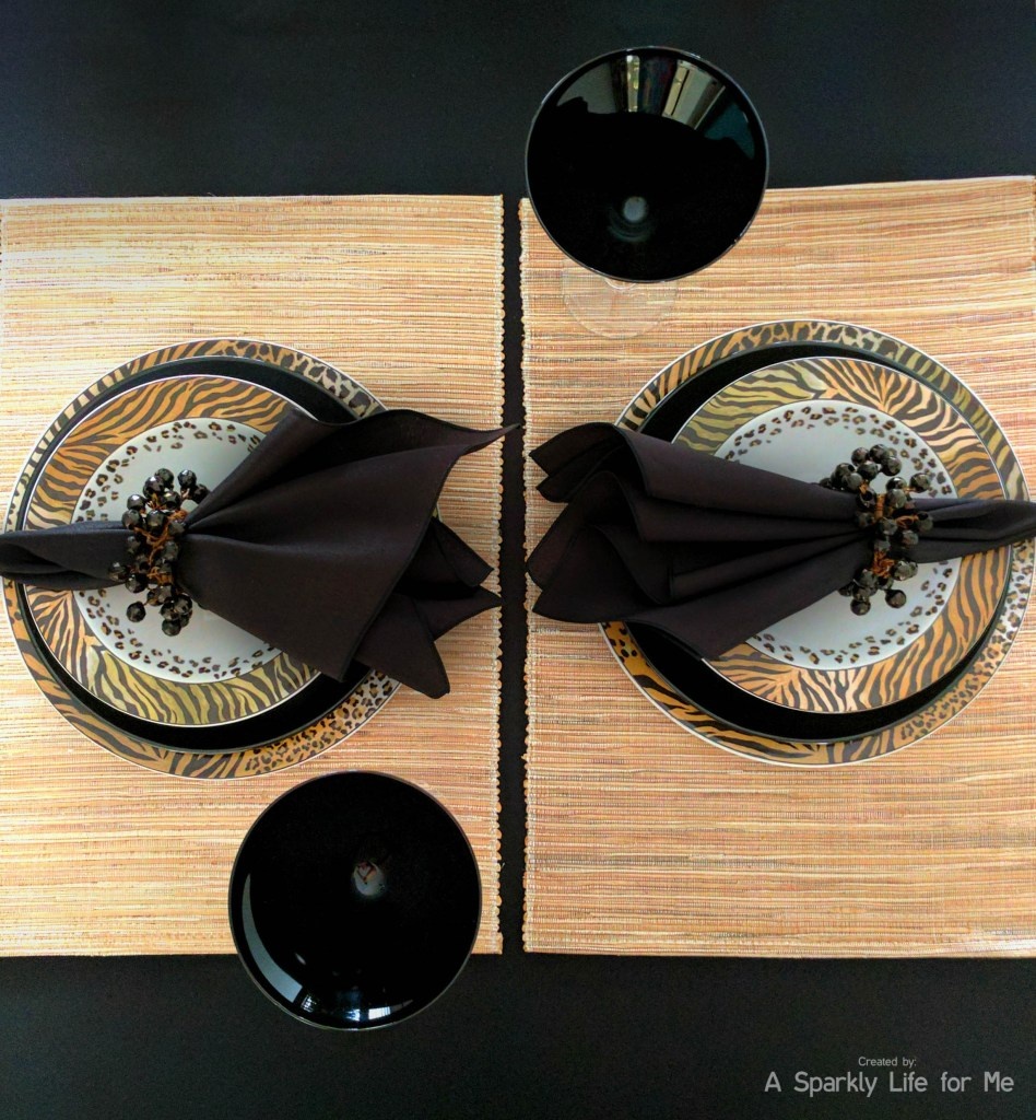 Animal print place settings for a jungle tablescape with bamboo woven placemats and black martini glasses