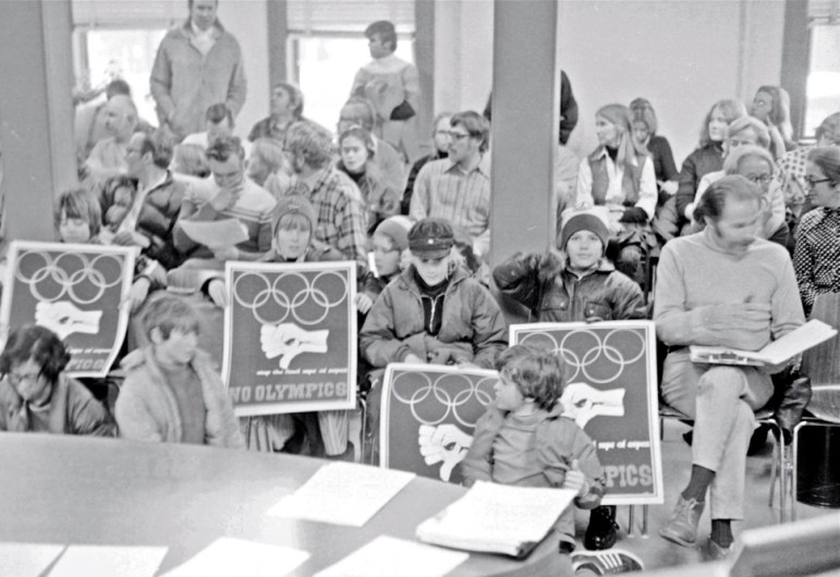 January, 1972, Aspen city council chambers. Aspen Times Editor Bil Dunaway, right, sits in his customary front-row seat. A former world class ski racer, he seems bemused by the anti-Olympics protest. In 1970, Denver and the Colorado mountains had been awarded the 1976 winter Olympics, but a protest against the games, and the growth they could bring, broke out in Colorado by '72. Eventually state voters rejected a funding question and the 1976 games were held in Innsbruck, Austria instead.