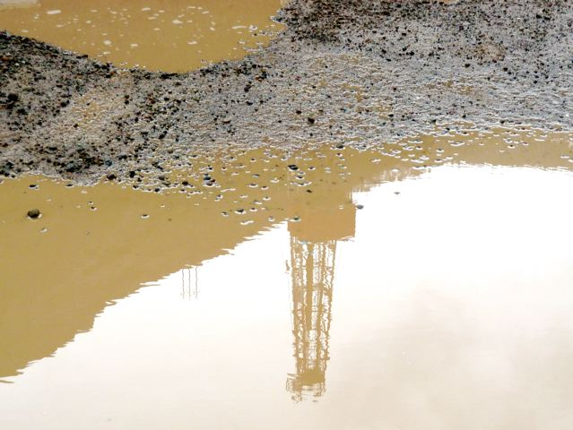The reflection of a gas drilling rig in a mud puddle near Parachute Creek on a rainy Saturday, April 9, 2011.